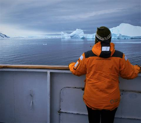Image Title: Enjoying the icebergs in the Bellingshausen Sea in a new polar explorer parka. [Photo: Open Door Travelers]
