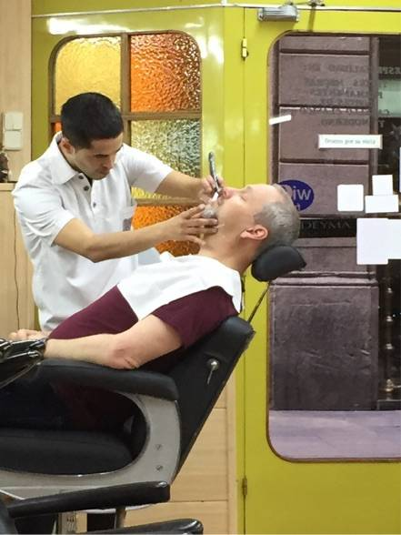 Image Title: Phil getting a close shave in #Barcelona, December 2015 {Photo: Open Door Travelers]